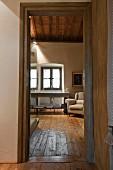 View through open door into bathroom with washstand below window and rustic wooden floor