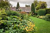 Taglilien und Grünpflanzen neben Rasenfläche in sommerlichem Garten mit bedecktem Himmel