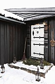 Lanterns in snow leading to black wooden hut with white front door