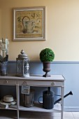 Lanterns and small bushes decorating console table against wall painted pastel yellow with pastel-blue wainscoting