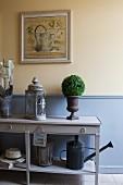 Konsolentisch mit Laterne und Dekobäumchen vor pastellblauer Wandverkleidung und pastellgelb getönter Wand
