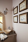 Washstand with countertop basin and modern tap in corner of bathroom next to collection of bicycle pictures on beige wall
