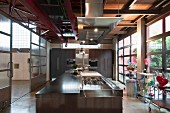 Modern designer kitchen in loft apartment with island counter, fitted appliances in background and view into hall