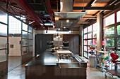 Moderne Designerküche in Loft, vorne Kücheninsel, Wand mit Einbaugeräten im Hintergrund und Blick in Halle