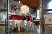 Blick durch Glasschiebetüren im Industrielook auf weissen Essplatz und Kugel-Lüster in Loftwohnung mit Galerie