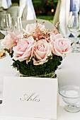 Namensschild vor Blumengesteck aus rosa Rosen, auf festlich dekoriertem Tisch