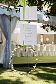 Geflochtener Kranz mit weissen Blüten und beschriebene Karten vom Baum hängend
