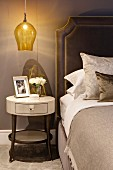 Round bedside table below pendant lamp with yellow glass lampshade next to bed with upholstered headboard