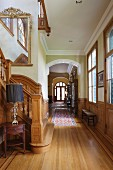 Foot of staircase and long hallway with panelled wainscoting in elegant villa