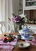 Suppenterrine & Schale mit Äpfeln auf Esstisch mit Lilienstrauss & Samt-Tischläufer