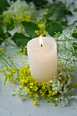 Lit pillar candle in wreath of rapeseed flowers and elderflowers