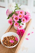 China bowl of hazelnuts and pot of daisies on wooden tray