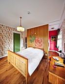 In nostalgischem Hotelzimmer Doppelbett mit geschnitztem Holzrahmen vor Raumteiler, seitlich Schreibtisch