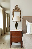 Bedside lamp on antique, marquetry bedside cabinet and mirror in bedroom with corridor along one side