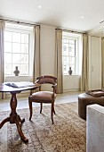 Antique upholstered chair at round table in elegant, traditional living area with floor-length curtains