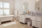Antique-style chest of drawers with twin sinks and claw-foot bathtub in elegant white bathroom