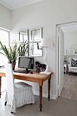 Schreibtisch mit Blume, Bildschirm, Pferdefiguren und Tischlampe, davor Hussenstuhl