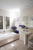 Badewanne mit breiter, gefliesten Ablage, Wandspiegel, blaue Flaschen und Blumensträusse