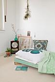 DIY-Tagesbett mit nostalgischem, gesticktem Kissen, Wanddeko mit Pfauenfedern und Retro Tischuhr in Zimmerecke