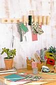 DIY-Wandleiste mit Möbelknöpfen und Holzklammern über Schreibtisch mit Bastelutensilien und Topfpflanze