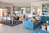 Blue corner sofa with scatter cushions and patterned rug in front of dining area with shell chairs and open-plan kitchen