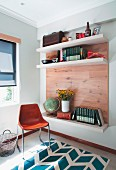 Shell chair next to shelving with wooden back wall and white shelves