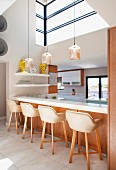 Bar stools with shell seats at white kitchen counter below pendant lamps and large, high windows
