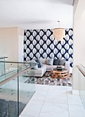 View from gallery with glass balustrade to corner seating area with chandelier and wallpaper with large leaf pattern