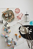 Party decorations - marshmallows skewered on twigs, pastel fairy lights and black and white striped paper cups