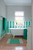 Dado in wide stripes of turquoise and white on bathroom wall behind free-standing bathtub