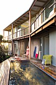 Pool integrated into wooden terrace outside house with timber-frame veranda and balcony