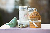 Romantic arrangement of quails' eggs, bird ornament, miniature bird cage and decorated screw-top jars