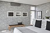 Elegantes Schlafzimmer mit Mustertapete und schwarz-weißem Farbkonzept