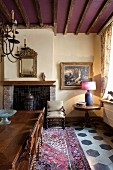 Tisch und Stühle mit gedrechselten Beinen auf Orientteppich in traditionellem Kaminzimmer, Holzbalken an violett getönter Decke