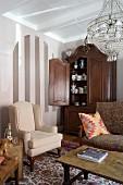 Traditionelle Wohnzimmerecke mit hellem Ohrensessel, antikem Schrank mit offener Tür und Blick auf Geschirr
