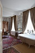 Cosy, vintage-style ensuite bathroom with free-standing bathtub, draped beige curtains, various Oriental rugs and toile de jouy wallpaper