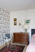 Antique chest of drawers and Rococo-style, elegant upholstered chair against wall with patterned wallpaper in corner of traditional bedroom