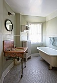 Marble washstand on wrought iron legs and free-standing vintage bathtub on mosaic-tiled floor