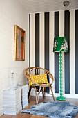 Rattanstuhl in Zimmerecke vor schwarz-weiss gestreifter Wand, und neben grüner Retro Stehleuchte