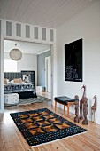 African sculpture and patterned rug on wooden floor in hallway leading to open sliding door with view into bedroom