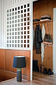 Table lamp with black lampshade on wooden floor in front of white partition screening cloakroom area at head of stairs