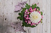Bouquet with white dahlia and snowberries on rustic wooden surface