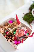 Christmas elf and baubles in box
