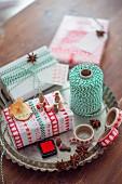 Weihnachtlich verpacktes Geschenk und Verpackungsutensilien in einer Tarteform