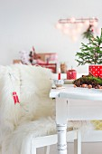 White fur blanket on chair next to small Christmas and lit candle on table