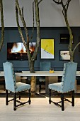 Chairs with black carved wooden frames and pale blue upholstery around table with integrated tree trunks