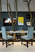 Stühle mit schwarzem, geschnitztem Holzgestell und hellblauem Polsterbezug vor Tisch mit eingebauten Baumstämmen