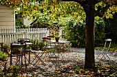 Tables and chairs in autumnal garden with white fence in background
