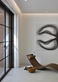 Designer chaise below modern artwork on wall in corner