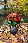 Bouquet of flowers in silver jug on autumn leaf litter